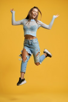 Wesoła dziewczyna w skoku podnosząca nogę do góry