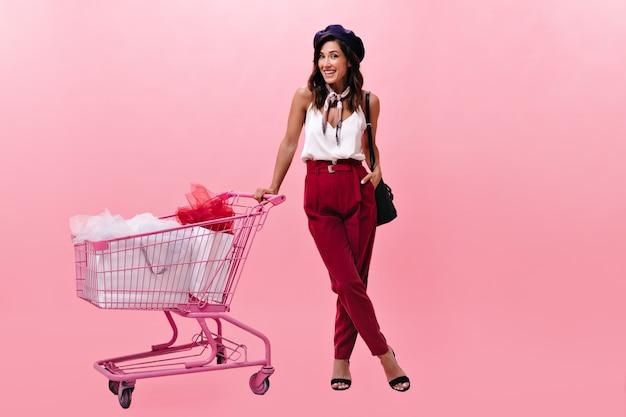 Wesoła dziewczyna w stylowe spodnie z wózkiem po zakupach. kobieta w modne jasne ubrania w berecie iz torebką uśmiecha się do kamery.
