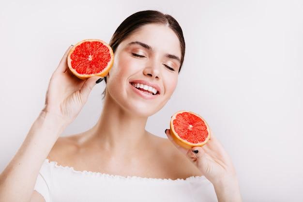 Wesoła dziewczyna w świetnym nastroju śliczna uśmiechnięta na białej ścianie, trzymając w rękach pyszne i smaczne owoce cytrusowe.