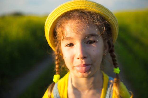 Wesoła dziewczyna w żółtym kapeluszu w letnim chuliganie polowym pokazuje język i dokucza. beztroska, radość, słoneczna pogoda, wakacje. styl życia, miła i śmieszna twarz, portret z bliska