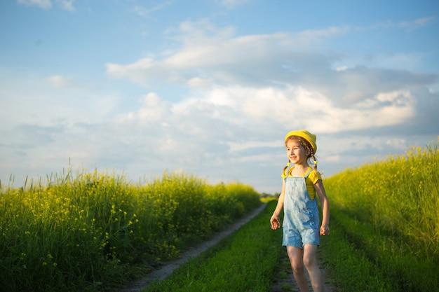 Wesoła dziewczyna w żółtym kapeluszu w letnim polu śmieje się i uśmiecha. radość, słoneczna pogoda, wakacje. środek na komary i owady. styl życia, miła twarz, portret z bliska, cieszenie się wolnością