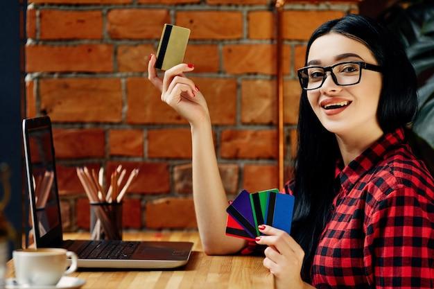 Wesoła dziewczyna z czarnymi włosami w okularach siedzi w kawiarni z laptopem, kartą kredytową i filiżanką kawy, koncepcja freelance, na sobie czerwoną koszulę.