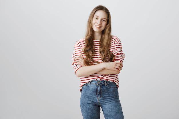 Wesoła dziewczyna z długimi włosami uśmiechnięty, skrzyżowane ramiona w klatce piersiowej pewny siebie