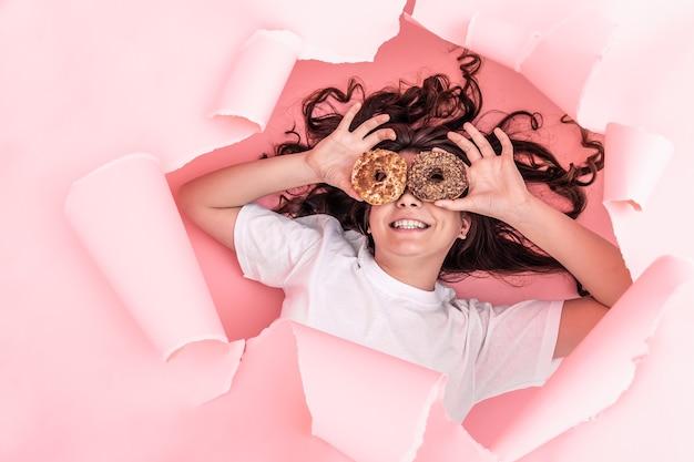 Wesoła dziewczyna z jasnymi pączkami na różowym tle papieru