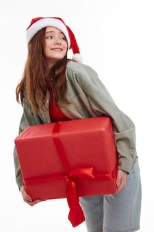 Wesoła dziewczyna z pudełkiem santa hat fun studio. wysokiej jakości zdjęcie