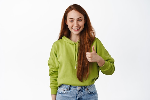 Wesoła dziewczyna z rudymi włosami, uśmiechnięta zadowolona, pokazująca kciuk w górę z aprobatą, lubi i chwali dobry wybór, dobra robota, stoi na białym