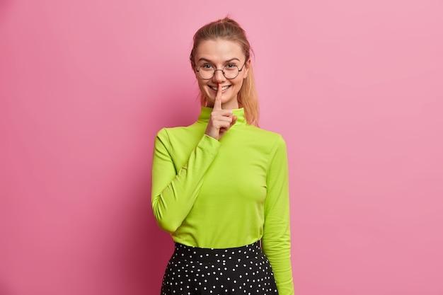 Wesoła dziewczyna z tysiąclecia przygotowuje niespodziankę dla kogoś, kto uśmiecha się czule, wykonuje gest ciszy, prosi o zachowanie tajemnicy, nosi okulary optyczne, swobodny golf
