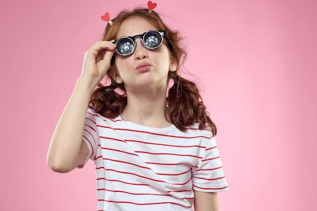 Wesoła dziewczyna z warkoczykami i okularami przeciwsłonecznymi w pasiastej koszulce