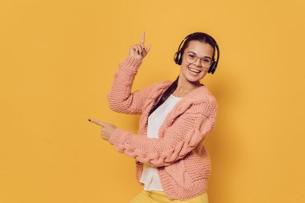 Wesoła dziewczyna ze słuchawkami na głowie, w różowym swetrze i żółtych spodniach, wskazująca do góry prawym palcem i na bok drugą ręką na żółtym tle. koncepcja reklamy sprzedaży.