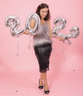 Wesoła dziewczyna ze srebrnymi balonami foliowymi w postaci cyfr