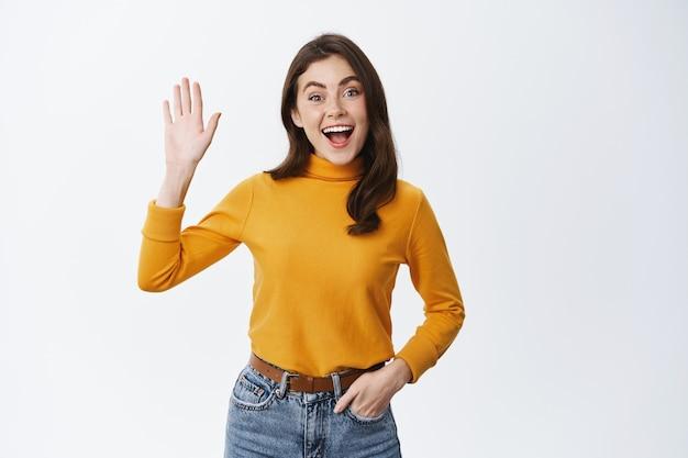 Wesoła dziewczyna żegna się lub pozdrawia, machając podniesioną ręką i patrząc w przód, stojąc na białej ścianie