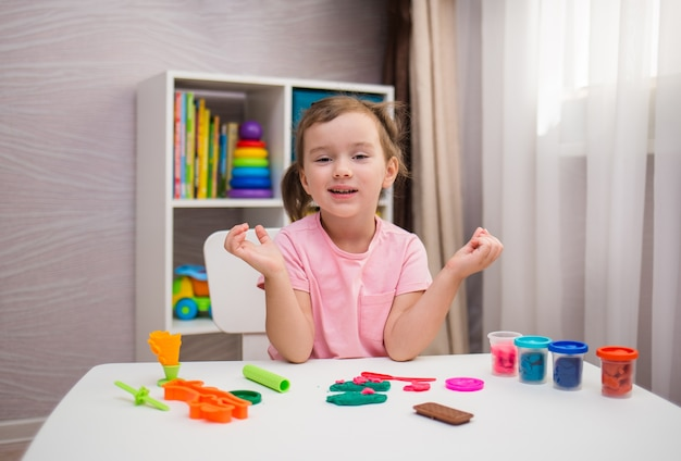 Wesoła dziewczynka bawi się plasteliną przy stole w pokoju