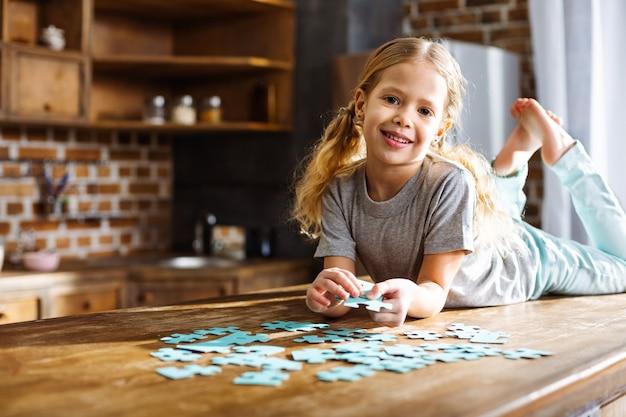 Wesoła dziewczynka bawi się puzzlami podczas odpoczynku w domu