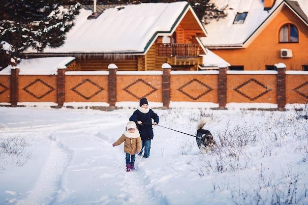 Wesoła dziewczynka i chłopiec spacerują z psem w parku w zimie