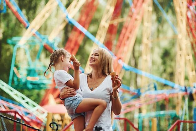 Wesoła dziewczynka, jej mama, bawi się razem w parku w pobliżu atrakcji