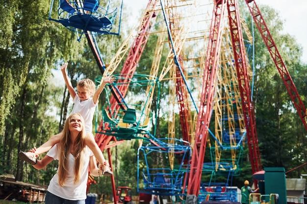 Wesoła dziewczynka jej mama dobrze się bawi w parku w pobliżu atrakcji.