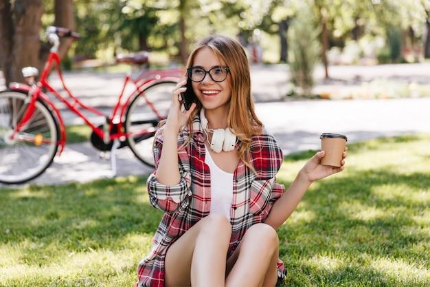 Wesoła dziewczynka kaukaski dzwoni do przyjaciela podczas picia kawy w parku. plenerowe zdjęcie inspirowanej damy odpoczywającej na trawie.