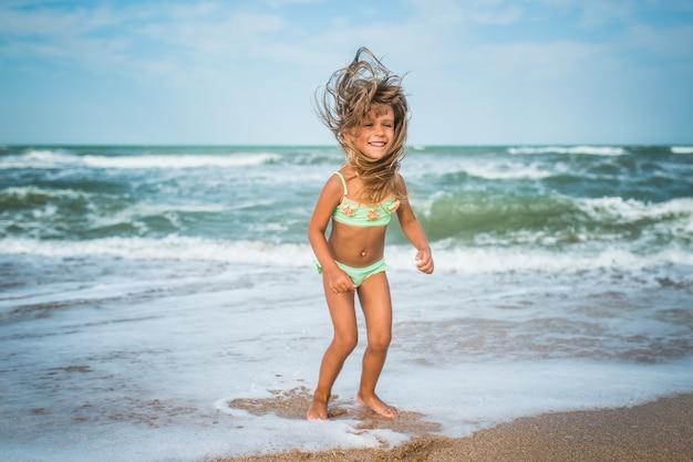 Wesoła dziewczynka kaukaski skacze i bawi się na falach morskich na piaszczystym wybrzeżu w słoneczny gorący letni dzień