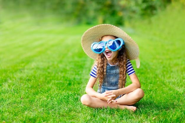 Wesoła dziewczynka latem na trawniku z dużymi śmiesznymi okularami przeciwsłonecznymi i słomkowym kapeluszem na zielonej trawie bawi się i raduje, miejsce na tekst