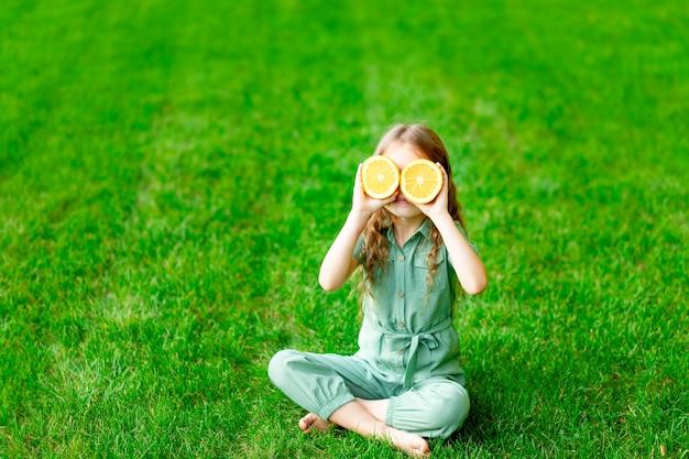Wesoła dziewczynka latem na trawniku zakryła twarz pomarańczami na zielonej trawie, bawi się i raduje, miejsce na tekst