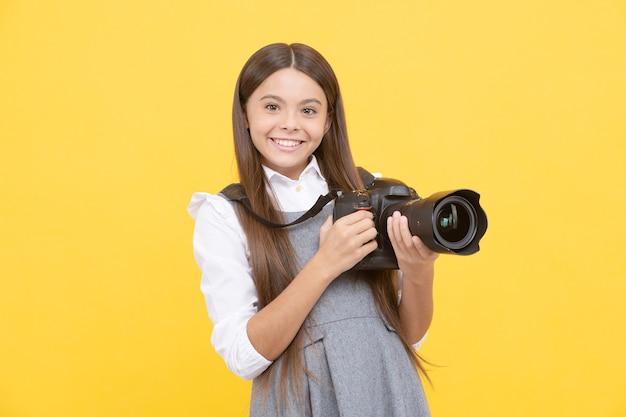 Wesoła dziewczynka robi zdjęcie aparatem cyfrowym, fotografia.