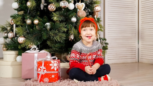 Wesoła dziewczynka siedzi pod ozdobioną choinką z pudełkami na prezenty, śmieje się ze słodyczami i pokazuje język