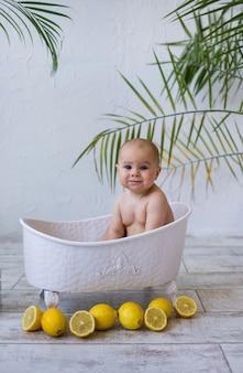 Wesoła dziewczynka siedzi w białej wannie z cytrynami na białym tle z miejscem na tekst. zabawne pływanie