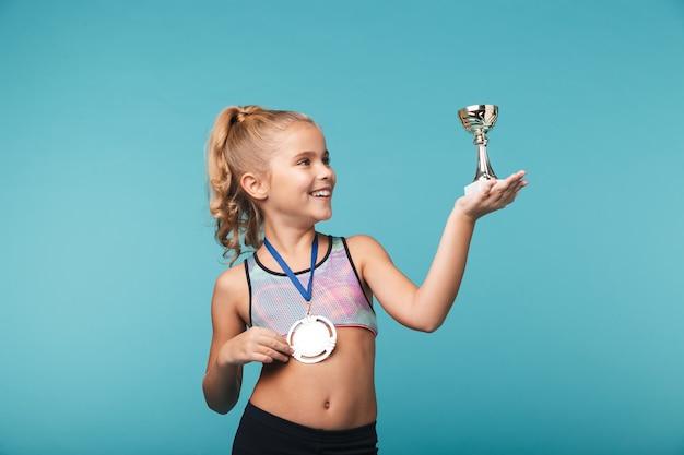 Wesoła dziewczynka sportowe świętuje zwycięstwo na białym tle nad niebieską ścianą, ubrana w złoty medal, pokazująca trofeum