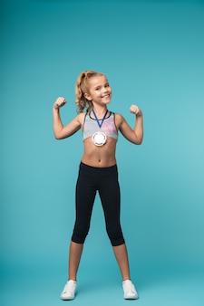 Wesoła dziewczynka sportowe świętuje zwycięstwo na białym tle nad niebieską ścianą, ubrana w złoty medal