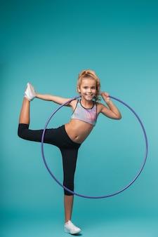 Wesoła dziewczynka sportowy robi ćwiczenia z hula hop na białym tle nad niebieską ścianą
