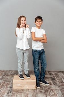Wesoła dziewczynka stojąca na pudełku obok wysokiego chłopca i świętująca sukces