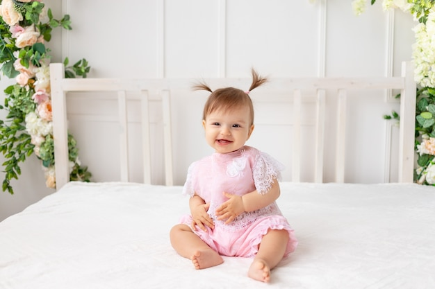 Wesoła dziewczynka sześć miesięcy siedzi w jasnym pięknym pokoju na białym łóżku w różowych ubraniach i uśmiecha się