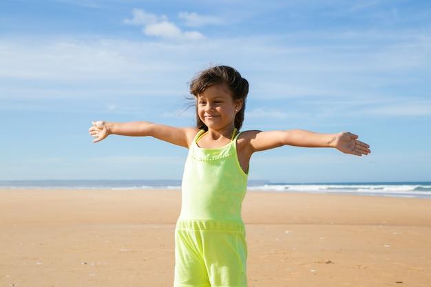 Wesoła dziewczynka ubrana w letnie ubrania, stojąc z otwartymi ramionami na plaży, odwracając wzrok
