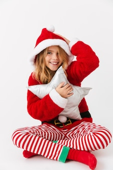 Wesoła dziewczynka ubrana w strój świąteczny siedzi na białym tle, trzymając poduszkę w kształcie gwiazdy