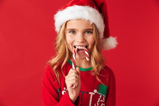 Wesoła dziewczynka ubrana w strój świąteczny stojący na białym tle, jedzenie cukierki christmas candy stożek