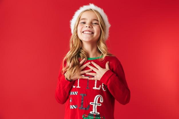 Wesoła dziewczynka ubrana w strój świąteczny stojący na białym tle, obchodzi