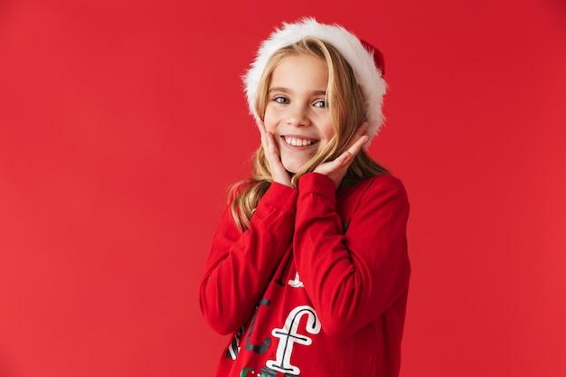 Wesoła dziewczynka ubrana w strój świąteczny stojący na białym tle, patrząc