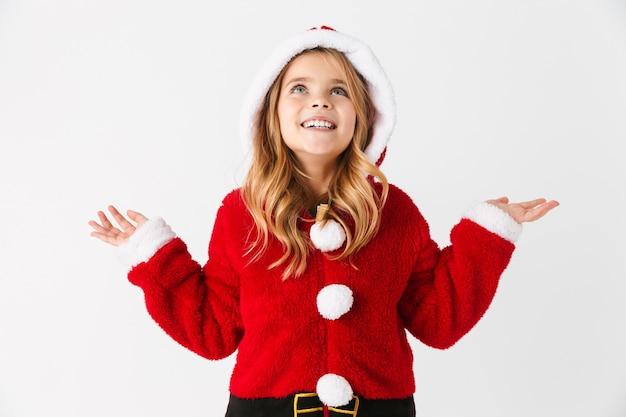 Wesoła dziewczynka ubrana w strój świąteczny stojący na białym tle, prezentując miejsce na kopię