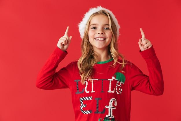 Wesoła dziewczynka ubrana w strój świąteczny stojący na białym tle, skierowaną w górę