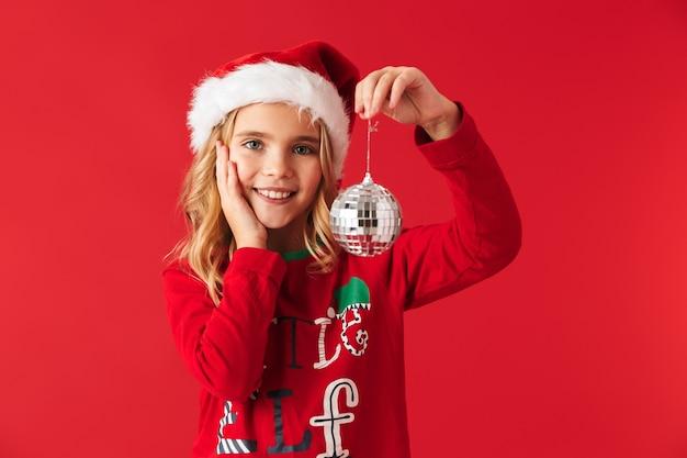 Wesoła dziewczynka ubrana w strój świąteczny stojący na białym tle, trzymając zabawki choinkowe