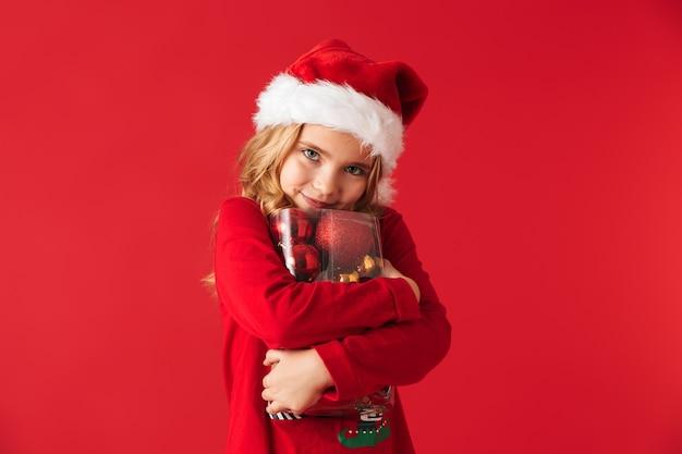 Wesoła dziewczynka ubrana w strój świąteczny stojący na białym tle, trzymając zestaw zabawek choinkowych
