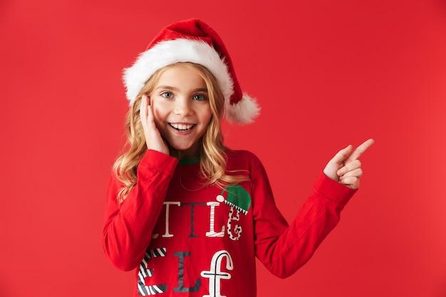 Wesoła dziewczynka ubrana w strój świąteczny stojący na białym tle, wskazując