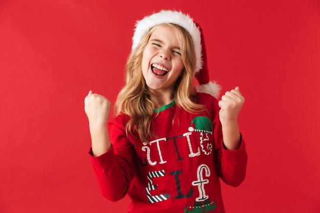 Wesoła dziewczynka ubrana w strój świąteczny stojący na białym tle