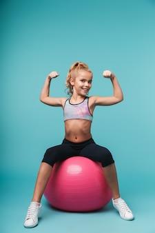Wesoła dziewczynka ubrana w stroje sportowe ćwiczeń z piłką fitness na białym tle nad niebieską ścianą
