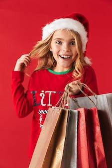 Wesoła dziewczynka w kapeluszu boże narodzenie stojących na białym tle, niosąc torby na zakupy