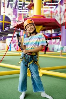 Wesoła dziewczynka w kasku pozuje na linii zip w centrum rozrywki. dzieci bawiące się na terenie wspinaczkowym, dzieciaki spędzają weekend na placu zabaw, szczęśliwe dzieciństwo