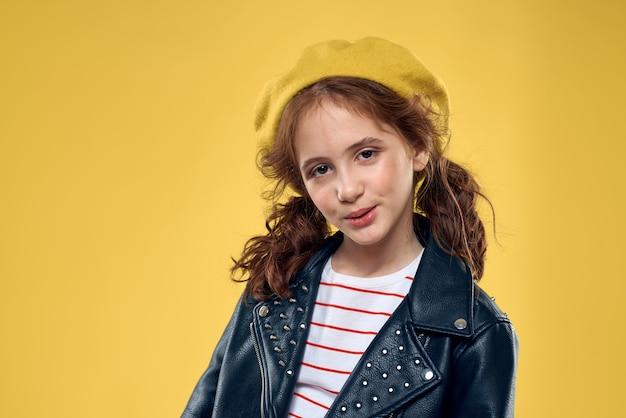 Wesoła dziewczynka w okulary przeciwsłoneczne i kapelusz stylu życia studio żółte tło mody