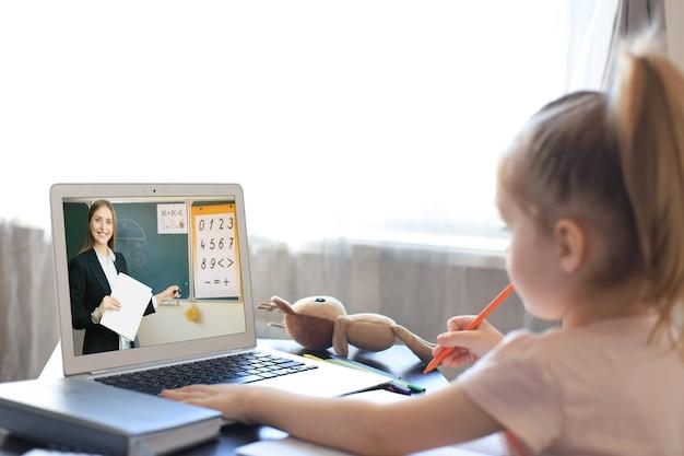 Wesoła dziewczynka w słuchawkach, korzystająca z laptopa, ucząca się przez system e-learningu online