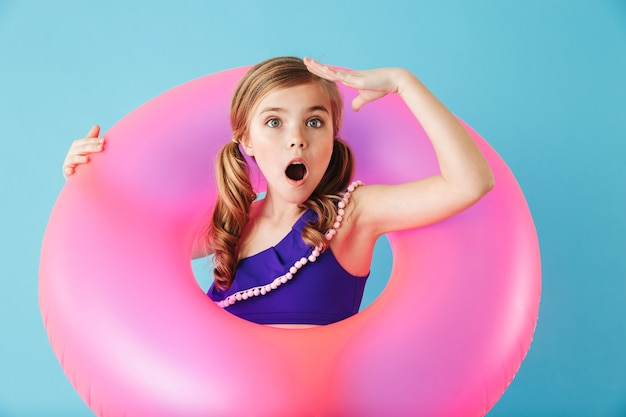 Wesoła dziewczynka w stroju kąpielowym stojąca na białym tle nad niebieską ścianą, bawiąca się nadmuchiwanym pierścieniem