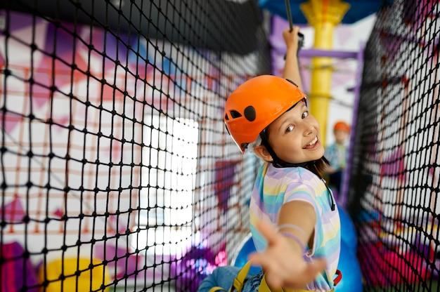 Wesoła dziewczynka wspina się na linach na linii zip w centrum rozrywki. dzieci bawiące się na terenie wspinaczkowym, dzieciaki spędzają weekend na placu zabaw, szczęśliwe dzieciństwo